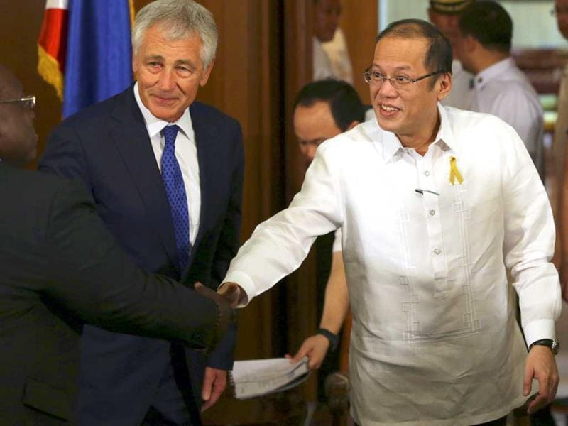 Philippine President Benigno Aquino III (R) shakes hands with US defence secretary Chuck Hagel (C) during his visit at the Malacanang Presidential Palace in Philippines. (AP Photo)