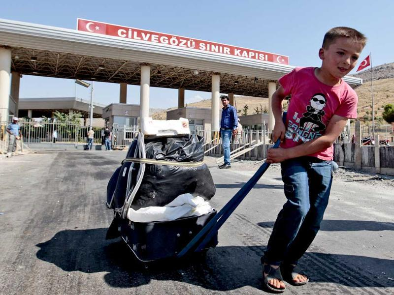 A child carries his belongings on a makeshift trolley through the Turkish Cilvegozu gate border. UN chemical weapons experts have left Syria and crossed into neighboring Lebanon. AP Photo