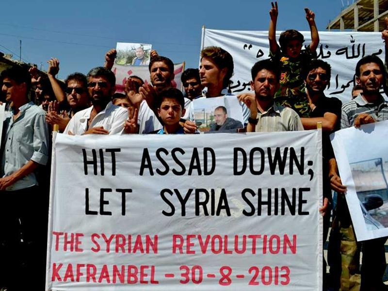 Anti-Syrian regime protesters carry a banner during a demonstration at Kafr Nabil town in Idlib province, northern Syria. AP photo