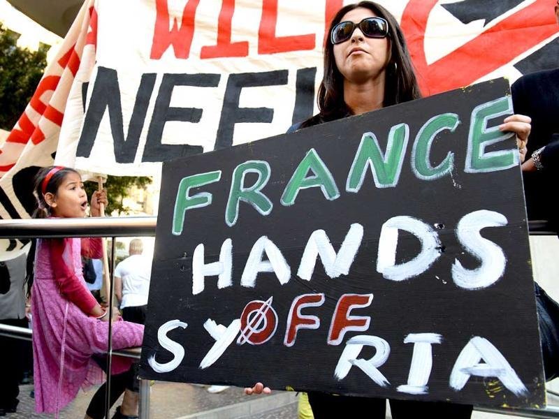 A woman holds a placard during a protest against a possible US military strike against Syria, in Sydney. AFP photo