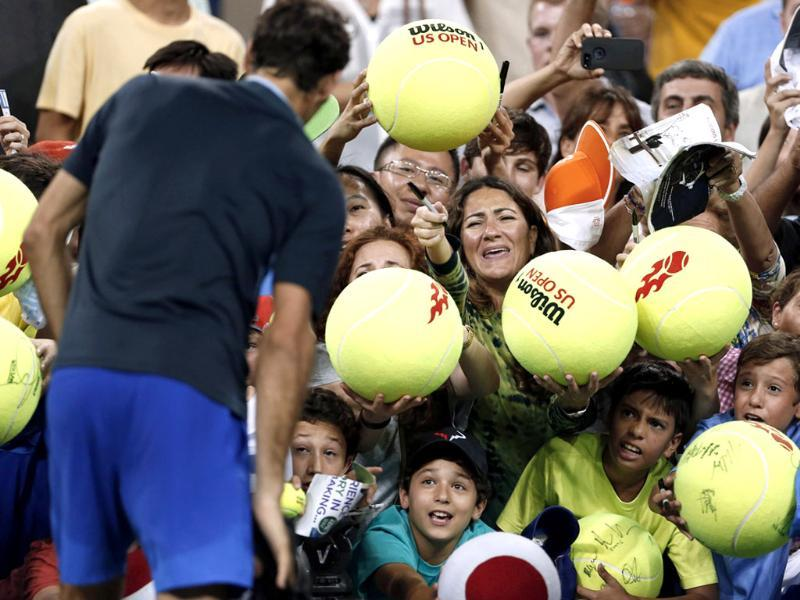 Roger Federer is hounded by autograph-seekers after defeating Adrian Mannarino at the US Open tennis championships in New York. (Reuters Photo)