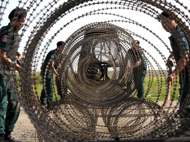 Cambodian policemen pull barbed wire as they block a street during a training exercise in Phnom Penh. (AFP Photo)