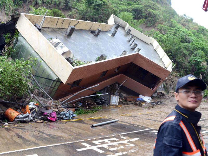 A policeman stands in front of a building damaged after heavy rains hit Taiwan's northern city of Keelung. (AFP Photo)