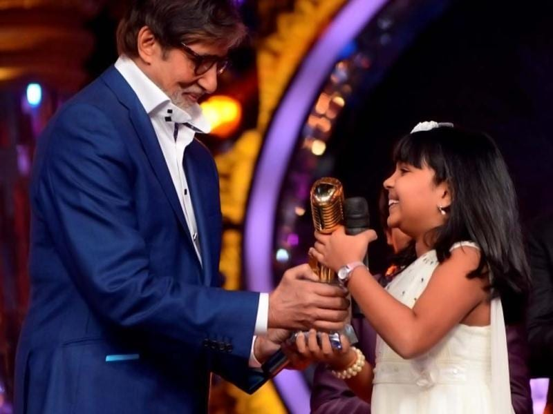 Amitabh Bachchan hands over the winner's trophy to Anjana Padmanabhan who's the first winner of the singing reality show Indian Idol Junior.