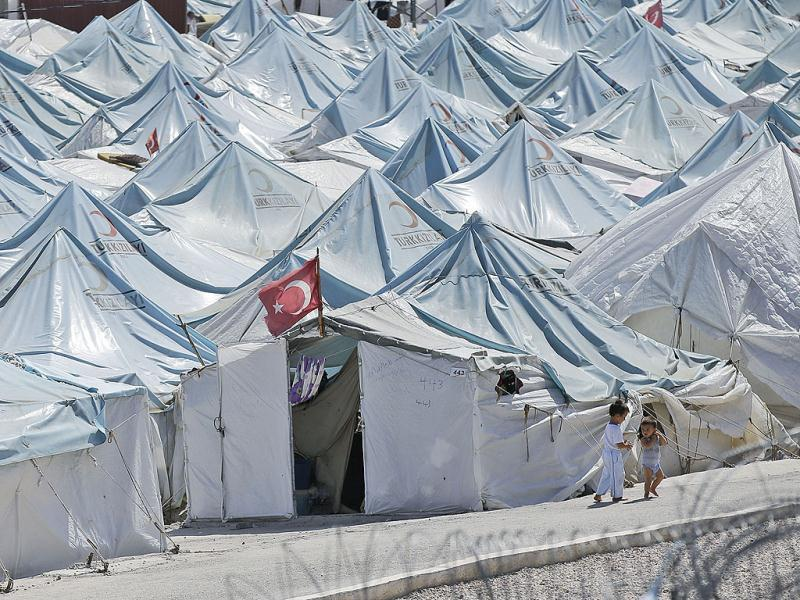 Children walk past tents of a Syrian refugees camp in Yayladagi, Turkey as the civil war in Syria has forced over 2 million people out of the country. AP photo