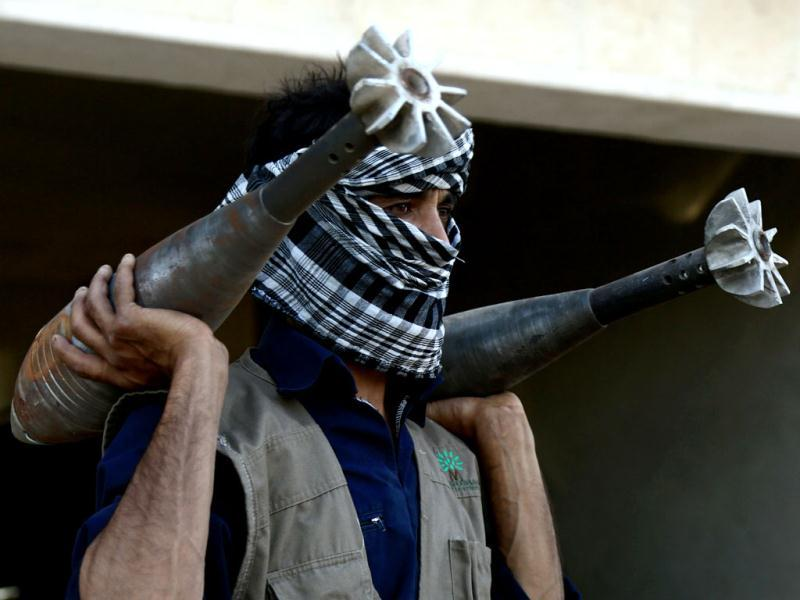 A rebel fightercarries homemade mortar rounds in the northern Syrian city of Raqqa. AFP