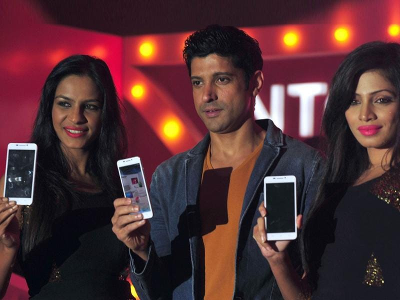 Farhan Akhtar poses with models holding the new Intex Aqua i7 phone at the launch event in Mumbai. Photo: AFP/Indranil Mukherjee