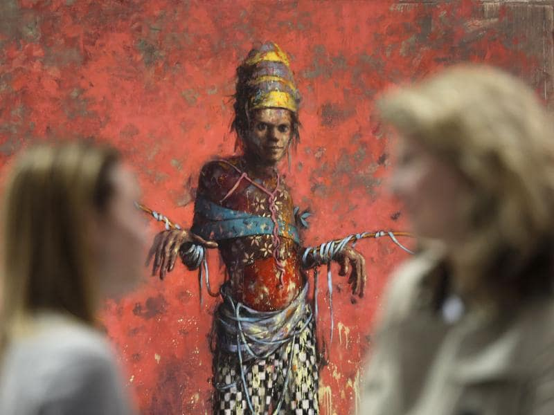Women talk in front of a painting by Jonas Burgert from the Blain Southern gallery during a private viewing of the ART Rio-International Art Fair in Rio de Janeiro, Brazil. (AP Photo)
