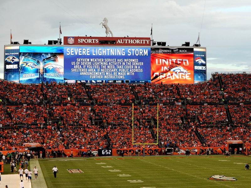 Fans wait in their seats as a weather delay is displayed on the jumbotron prior to the game between the Denver Broncos and the Baltimore Ravens at Sports Authority Field in Denver Colorado. AFP photo