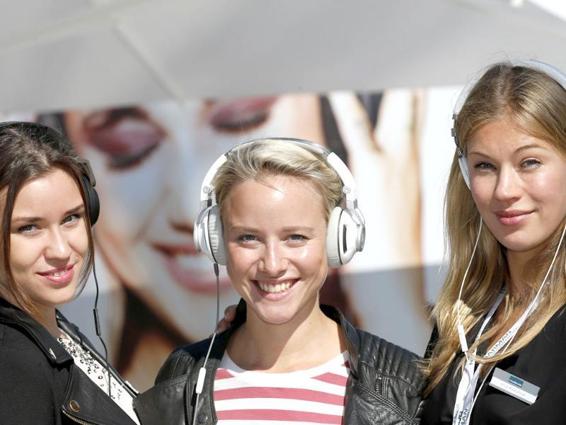 Models pose with the new AKG K545 (L-R), JBL Synchros S300 and Harman/Kardon Soho headphones at the IFA consumer electronics fair in Berlin. Photo: Reuters/Fabrizio Bensch