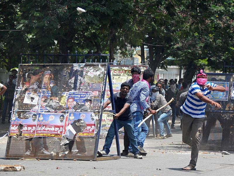 Pro-Telangana Osmania University students hurl stones towards police during the protest against 'Save Andhra Pradesh' meeting. (AFP Photo)