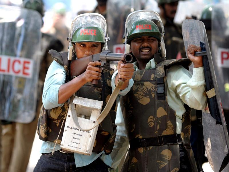 A policeman takes aim with a tear gas round against pro-Telangana students in Hyderabad. (AFP Photo)