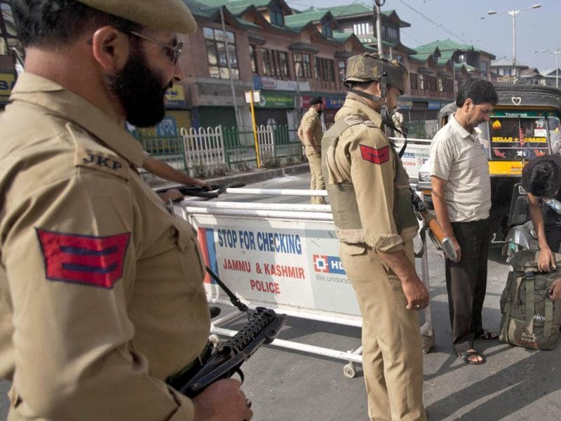 Police officers check the bags of commuters at a checkpoint during a strike in Srinagar. (AP Photo)