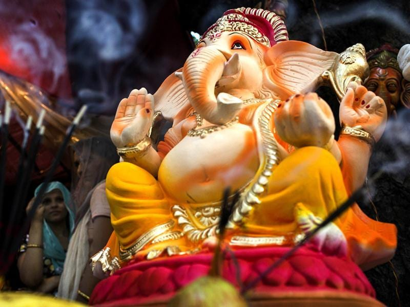 An artist stands near Ganesh idols for sale on the first day of the Ganesh Chaturthi festival in New Delhi. (AFP Photo)