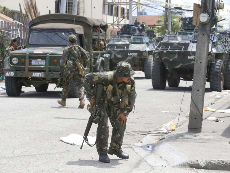 Government troopers, backed by armored personnel carriers, position themselves at an intersection at the southern port city of Zamboanga in southern Philippines. (AP Photo)