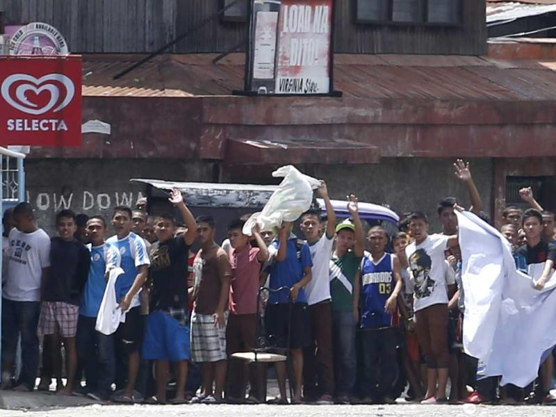 Residents believed to be hostages of Moro National Liberation Front rebels wave white cloth and shout to the government soldiers