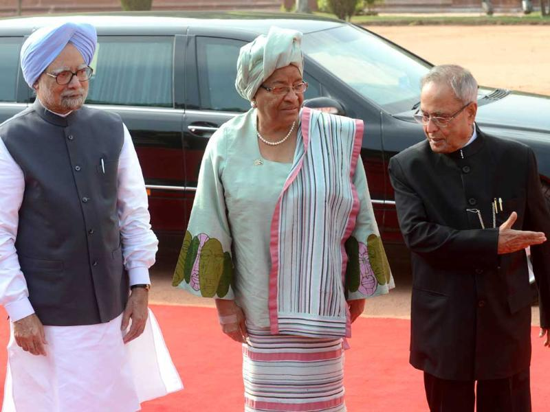 President Pranab Mukherjee is watched by Prime Minister Manmohan Singh as he welcomes Liberian President Ellen Johnson-Sirleaf to a welcome ceremonial at The Presidential Palace in New Delhi. (AFP Photo)