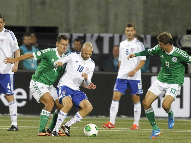 Faroe Islands' Christian Holst is challenged by Germany's Miroslav Klose and Thomas Mueller during the group C World Cup qualifying soccer match between Faroe Islands and Germany in Torshavn, Germany. (AP Photo)