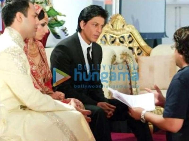 SRK is chatting with the bride and groom at the wedding. (Photo: Bollywood Hungama)