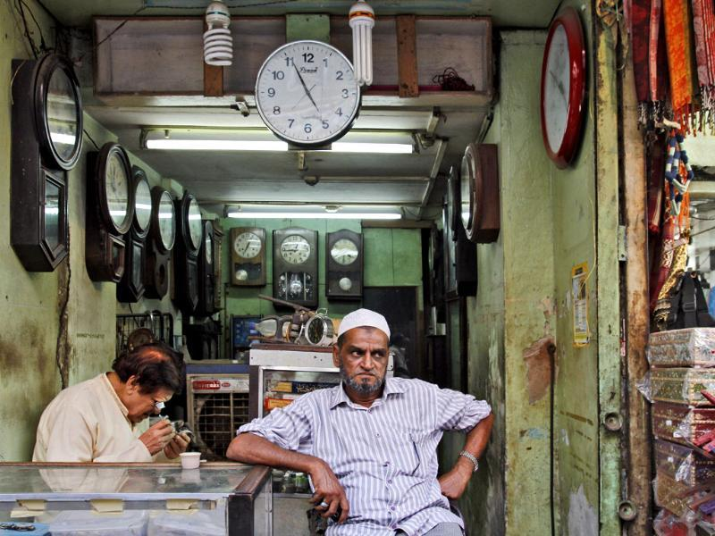 Mohammad Rafique, an old man, repairs watches at his 150 year old shop in the old quarters of Delhi while his customer waits outside. (Subrata Biswas/HT Photo)