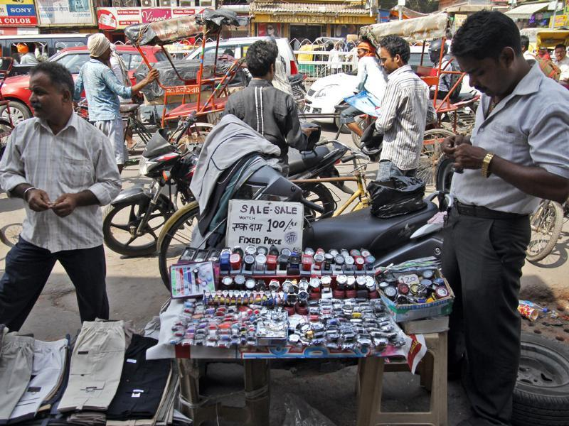 Potential customers check out modern watches at a roadside kiosk in Nehru Place, New Delhi. (Subrata Biswas/HT Photo)