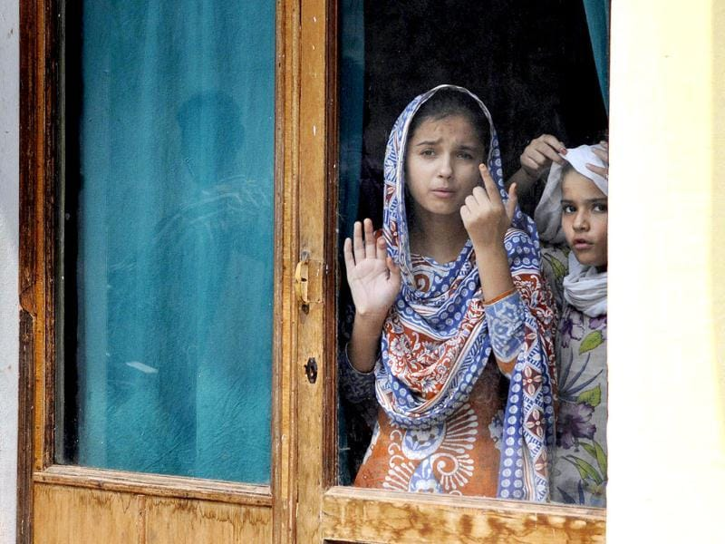 Two girls looking through a glass door after the curfew was lifted at Shahpur village, after communal violence in Muzaffarnagar. (Sushil Kumar/HT)