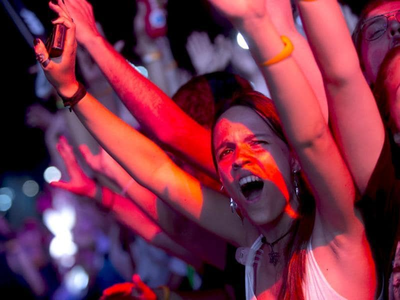 Cheering fans, bathed in red light, enjoy the performance by Brazilian band Capital Inicial at the annual Rock in Rio music festival in Rio de Janeiro. (AP Photo)
