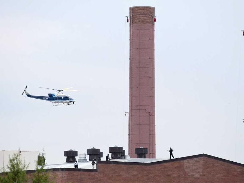 A police helicopter flies overhead as police walk on the roof of a building as they respond to a shooting at the Washington Navy Yard in Washington. (Reuters Photo)