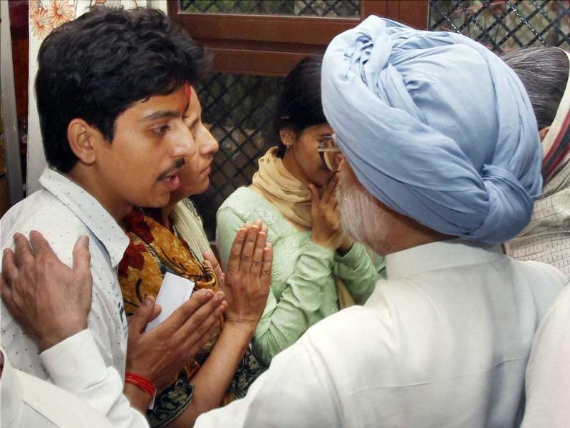 Prime Minister Manmohan Singh consoling the family members of a journalist who was killed in the riots, in Muzaffarnagar district on Monday. (PTI Photo)