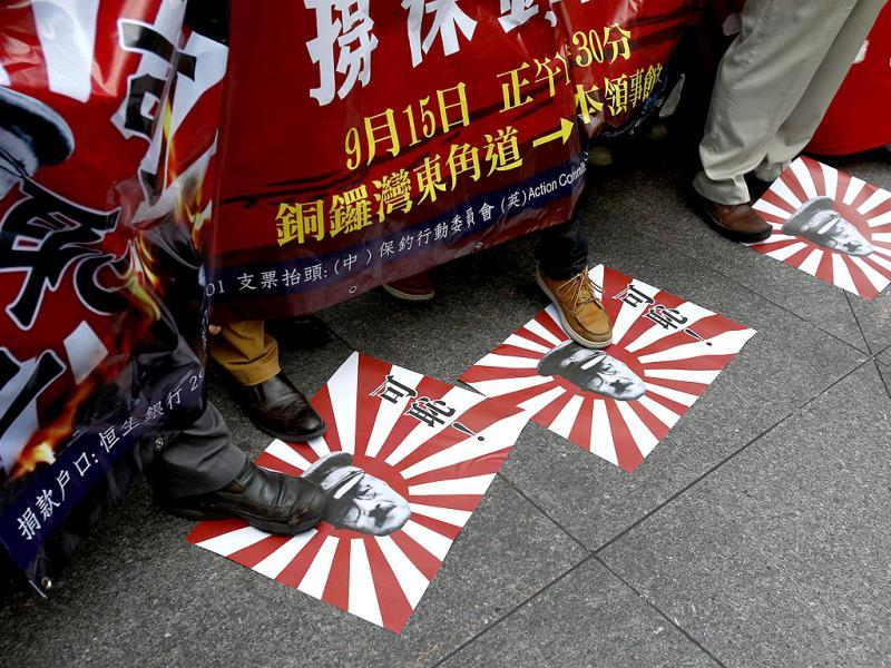 Protesters step on illustrations of Japanese military flags featuring a portrait of Hideki Tojo, former general of the Imperial Japanese Army and Prime Minister of Japan during World War II, at a protest outside the Japanese consulate in Hong Kong on the 82nd annivesary of the Manchurian Incident which marked Japan's invasion to China. (Reuters)