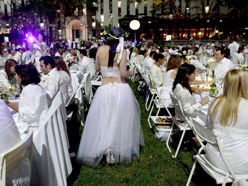 Guests are seated for dinner at a chic secret pop-up style picnic, held always a landmark location and revealed at the last-minute. (AFP Photo)