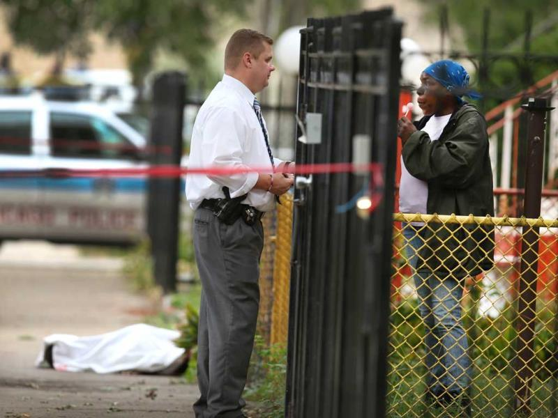 A police officer investigates the shooting death of 14-year-old Tommy McNeal, whose body is covered by a sheet in Chicago, Illinois. (AFP PHOTO)