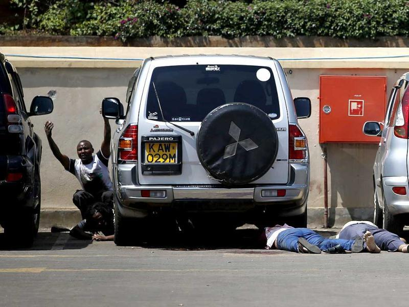 People come out from hiding under a car next to bodies in a car park as police search for gunmen in Westgate shopping centre in Nairobi, Kenya. (Reuters Photo)