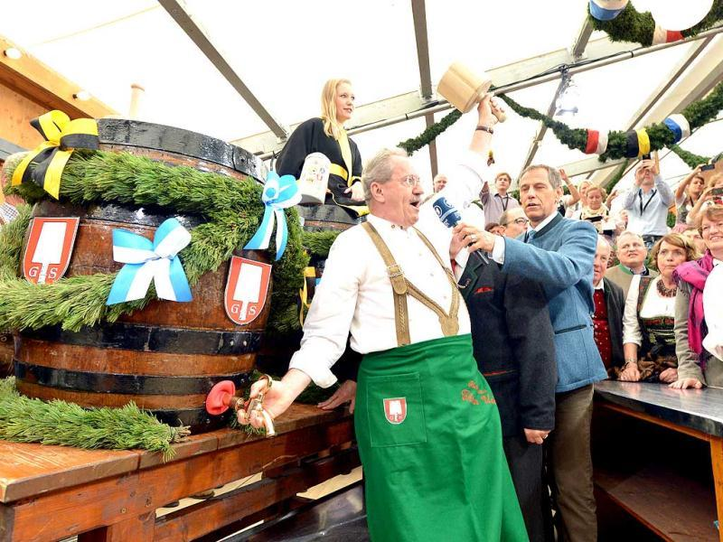 Munich's Mayor Christian Ude taps the first barrel of beer with the traditional