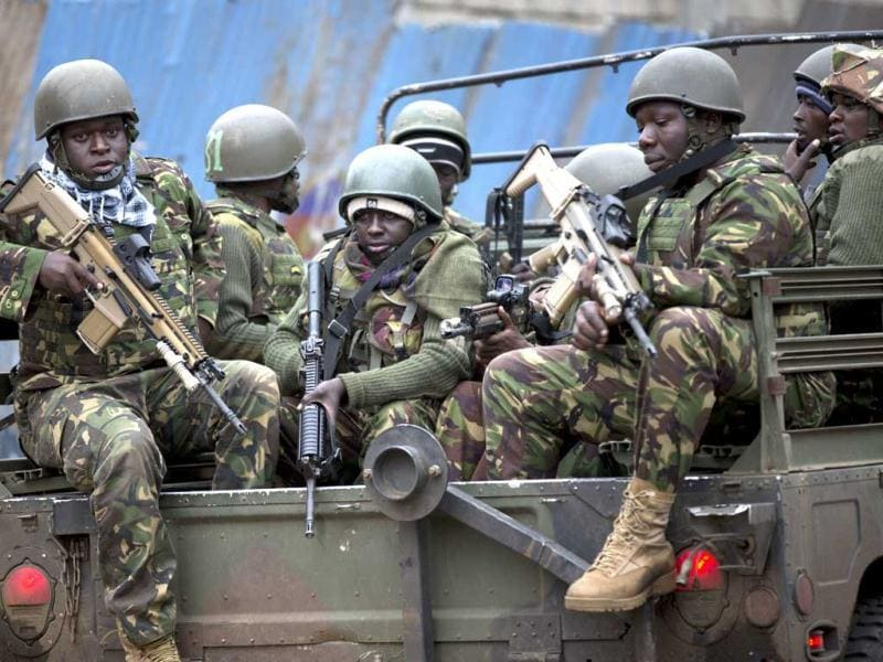 Trucks of soldiers from the Kenya defence forces arrive after dawn outside the Westgate Mall in Nairobi. (AP Photo)