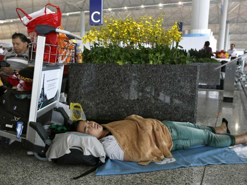 A passenger sleeps at Hong Kong's international airport as flights remain delayed following the year's most powerful typhoon slammed into southern China, forcing hundreds of flight cancellations (AP Photo)