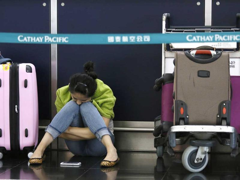 A passenger waits for flights to resume while sitting an airline counter at Hong Kong's international airport after Typhoon Usagi slammed into southern China. (AP Photo)