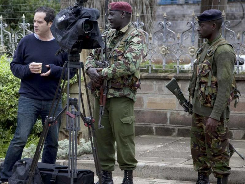 Kenyan security personnel ask journalists to clear the area outside the Westgate mall after firing started inside. (AP Photo)
