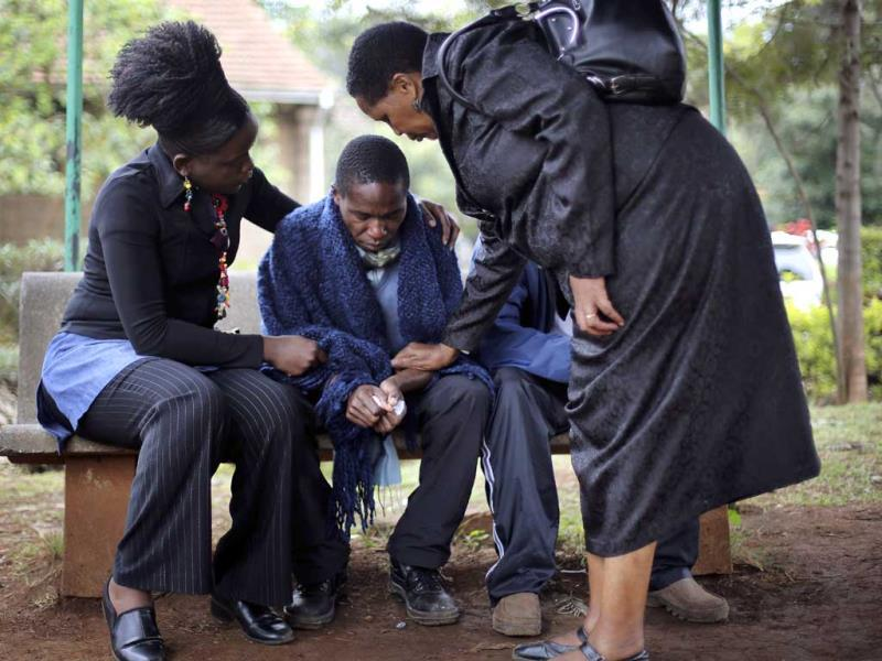 Stephen, centre, who lost his father in Saturday's attack at the Westgate mall in Nairobi, is comforted by relatives as he waits for the post mortem exam at the city morgue. (AP Photo)