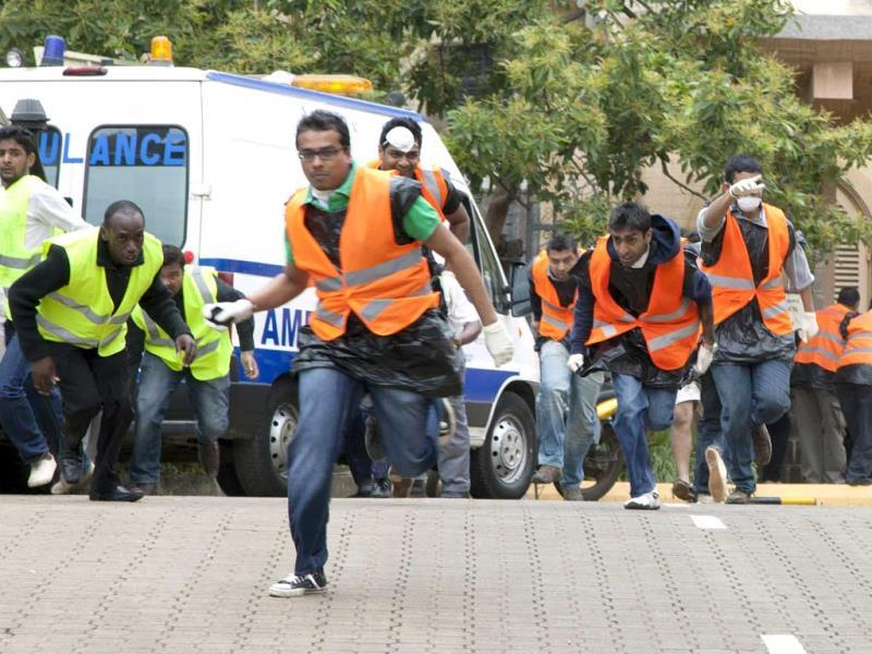 Paramedics run outside the Westgate mall in Nairobi after heavy shooting started. (AP Photo)