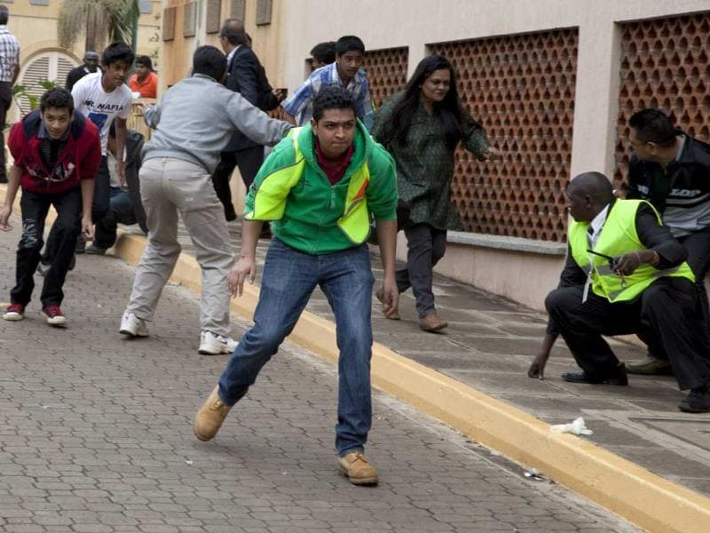 People take cover outside the Westgate mall in Nairobi after heavy shooting started. (AP Photo)