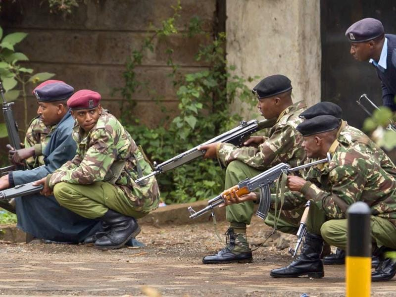 Armed police from the General Service Unit take cover behind a wall during a bout of gunfire, outside the Westgate mall in Nairobi, Kenya. (AP Photo)