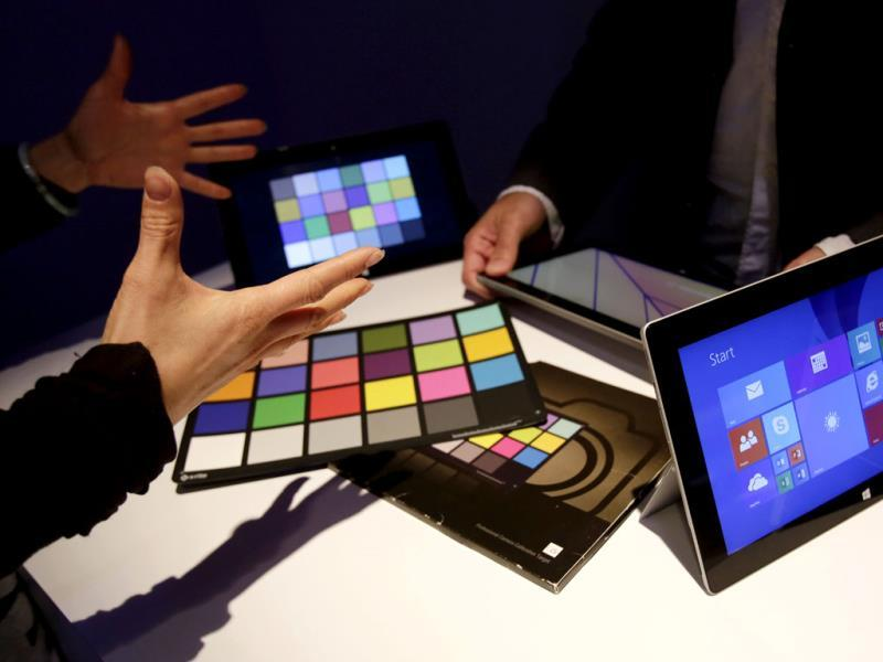 People discuss the Surface 2 tablet computer at its introduction in New York. Microsoft is trying hard to succeed in tablets as personal computer sales are falling. Photo: AP/Mark Lennihan
