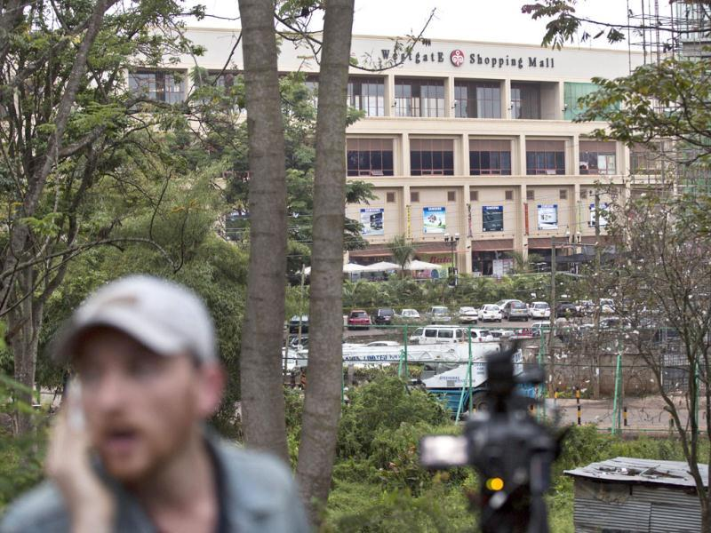 A television reporter makes a telephone call while filming during a bout of heavy gunfire shortly after dawn, at the Westgate Mall in Nairobi. (AP Photo)