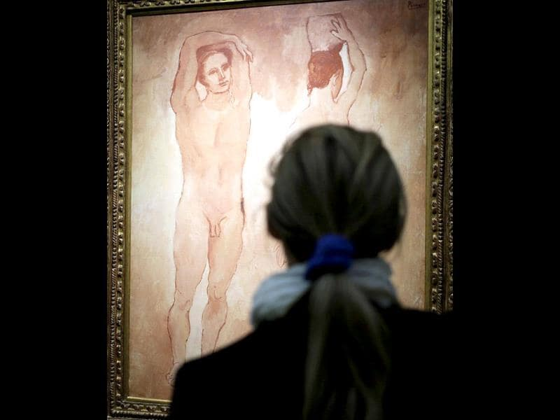 A visitor looks at the painting Les adolescents (Teenagers) by Spanish artist Pablo Picasso. (AFP Photo)