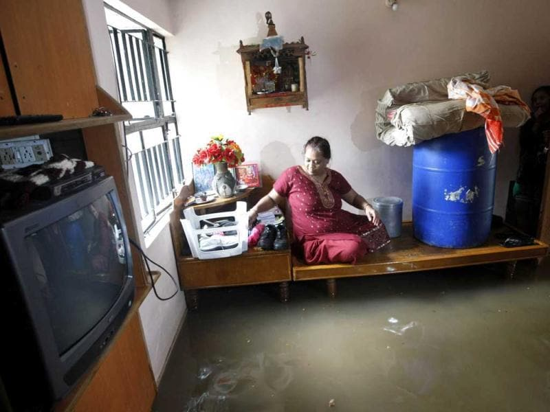 A woman sits on a bed inside her flooded room after heavy rains in Ahmedabad. (Reuters Photo)