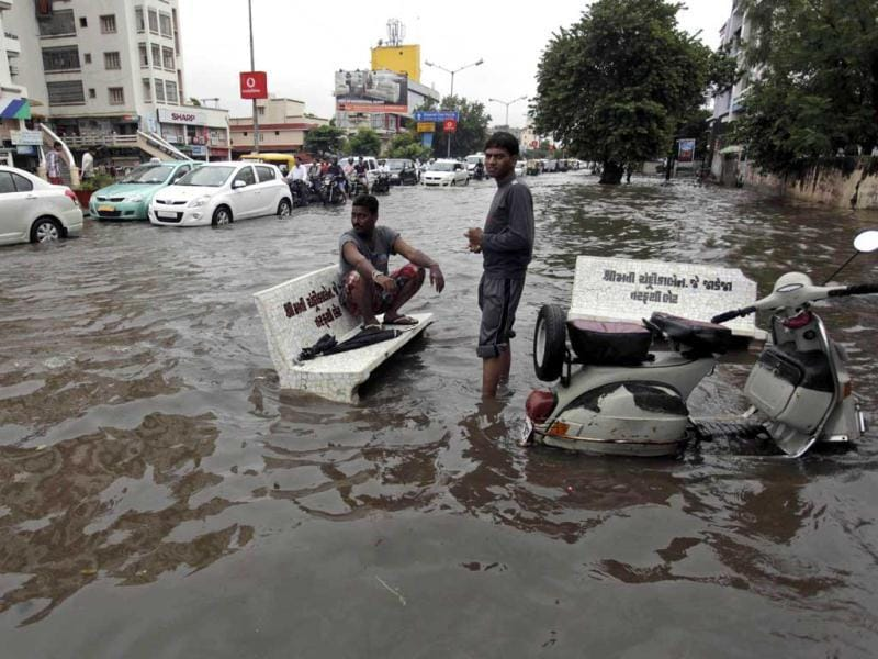 A man sits on a stone bench as motorists drive past a flooded street after heavy rains in Ahmadabad. (AP Photo)