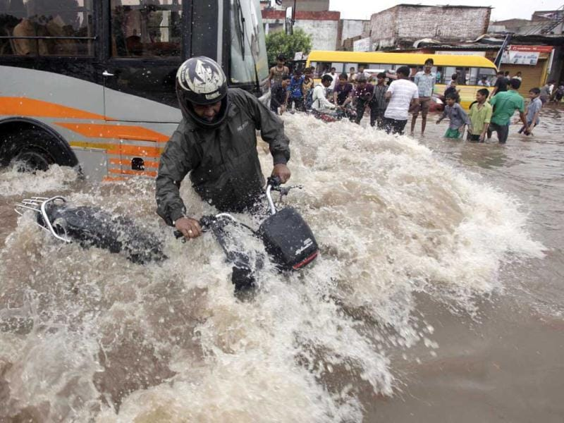 A motorist tries to balance himself as a bus drives past him on a flooded road after heavy rains in Ahmadabad. (AP Photo)
