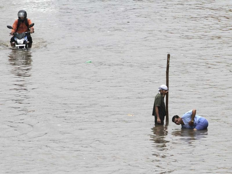 Men clean blocked sewerage line to drain out flooded water from a road after heavy rains lashed, in Ahmadabad. (AP Photo)