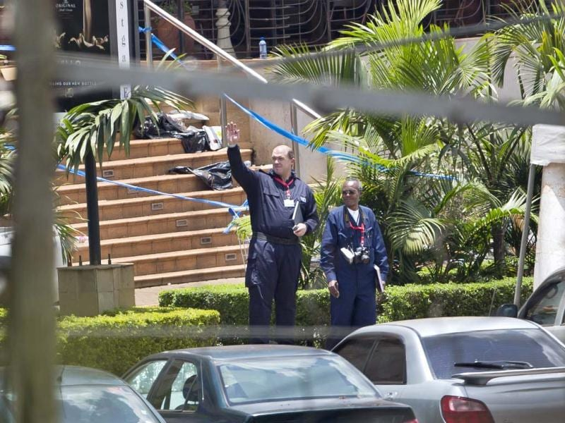 An unidentified foreigner involved in the forensics investigation gestures to another as they inspect the scene in front of the Westgate Mall in Nairobi, Kenya. (AP Photo)